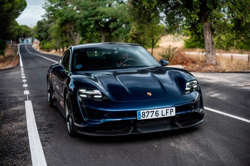 Porsche Taycan 2020 azul en la carretera cruzando un bosque